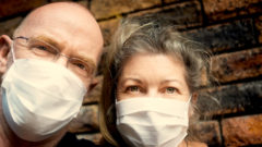 Surgical masks worn as a defense against the spreading pandemic of the coronavirus that causes COVID-19.